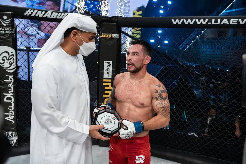1.Ray Borg receives his award from Abdulmunam Al Hashemi, chairman of Palms Sports, in the UAE Warriors 20 at the Jiu-Jitsu Arena in Abu Dhabi on Saturday, June 19, 2021. Photo: UAE Warriors