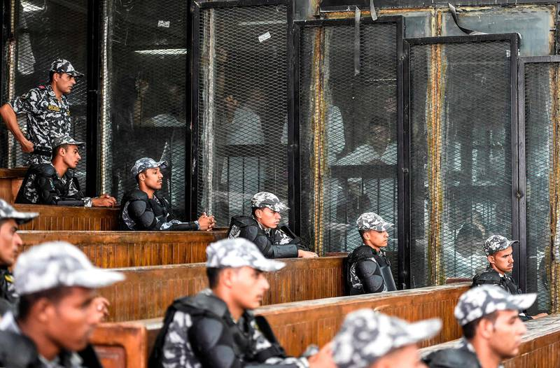 Members of Egypt's banned Muslim Brotherhood are seen inside a glass dock during their trial in the capital Cairo on July 28, 2018.  / AFP / Khaled DESOUKI
