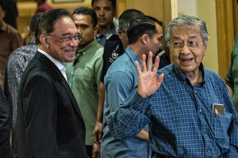 epa08019158 Malaysian Prime Minister Mahathir Mohamad (R) waves to the media, as prime minister in-waiting Anwar Ibrahim (L) smiles, after a press conference held at the conclusion of a presidential council meeting in Putrajaya, Malaysia, 23 November 2019.  EPA/AHMAD YUSNI