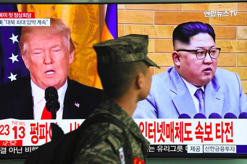 TOPSHOT - A South Korean soldier walks past a television screen showing pictures of US President Donald Trump (L) and North Korean leader Kim Jong Un at a railway station in Seoul on March 9, 2018.  US President Donald Trump agreed on March 8 to a historic first meeting with North Korean leader Kim Jong Un in a stunning development in America's high-stakes nuclear standoff with North Korea. / AFP PHOTO / Jung Yeon-je