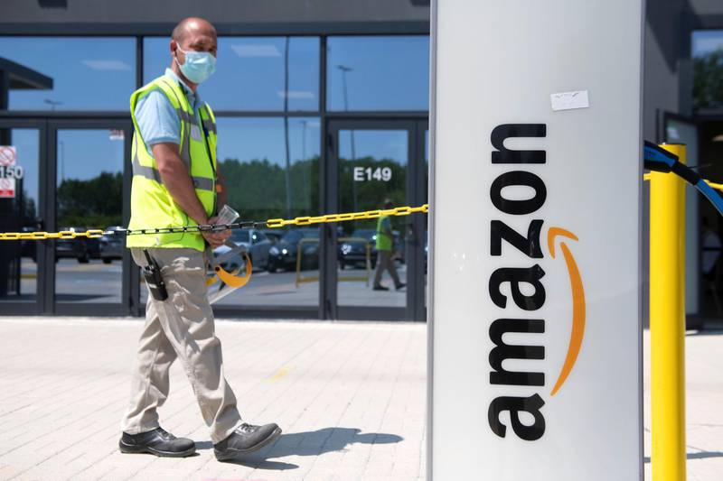 TORRAZZA PIEMONTE, ITALY - JUNE 03: Man walks near of Amazon logo in Amazon Headquarter on June 03, 2021 in Torrazza Piemonte near Turin, Italy. Amazon Italy rolls out an on-site vaccine site for its employees. as Italy steps up next wave of vaccine campaigns. (Photo by Stefano Guidi/Getty Images)