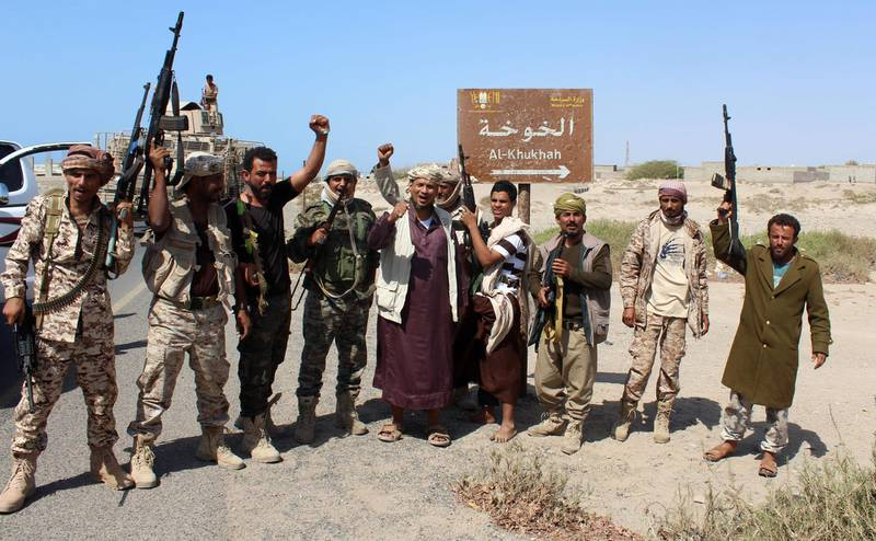 (FILES) A file photo taken on December 10, 2017 shows Yemeni fighters loyal to the Saudi-backed Yemeni president gesturing and shout slogans as they stand on a road leading to the town of Khokha which was retaken from Shiite-Huthi rebels, about 120 kilometres south of the Huthi rebel-held Red Sea port of Hodeida.  / AFP / SALEH AL-OBEIDI