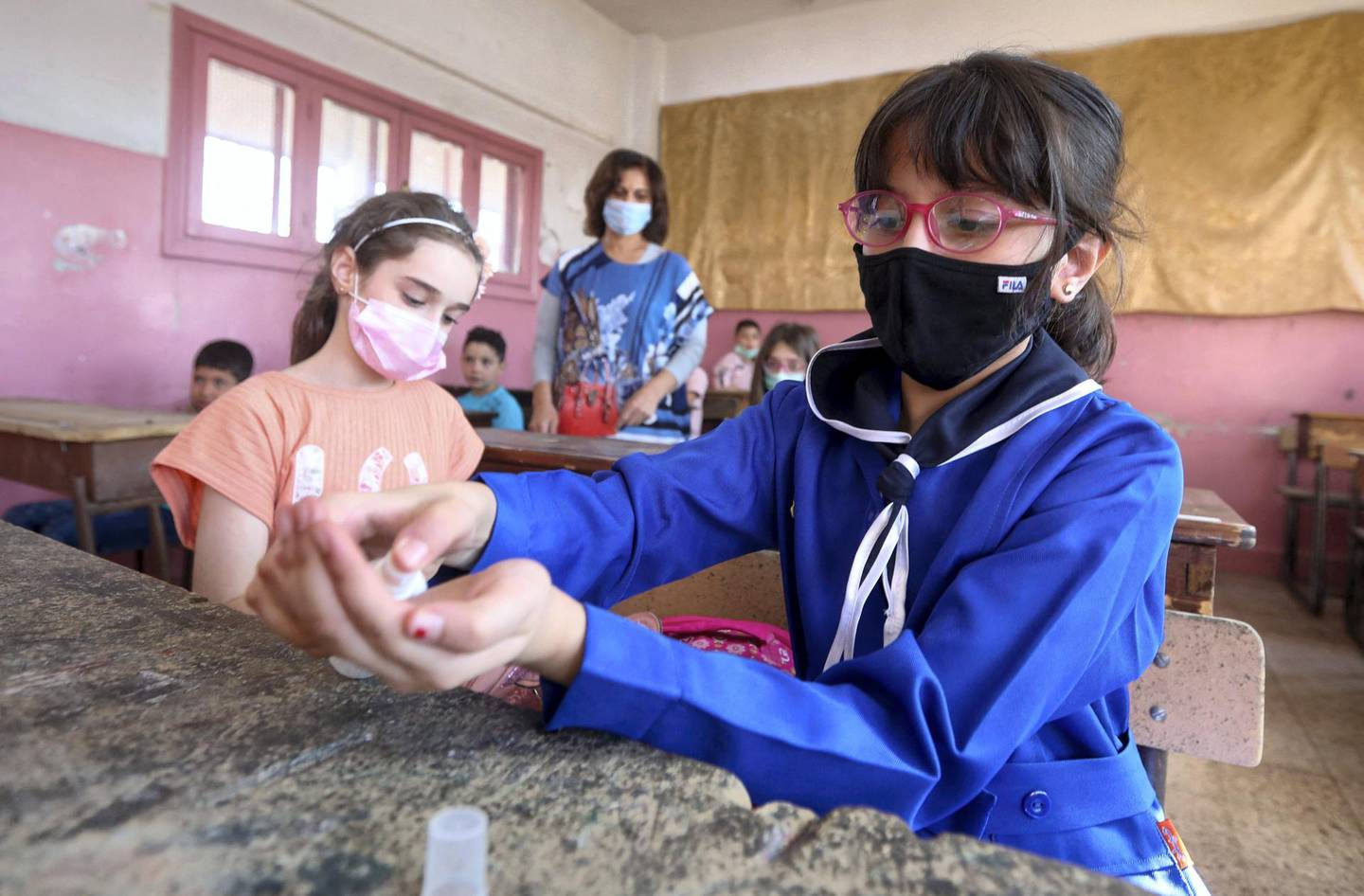 Syrian pupils, some wearing protective face masks, disinfect their hands in class in the capital Damascus on September 13, 2020, during the first day of the school year. (Photo by LOUAI BESHARA / AFP)