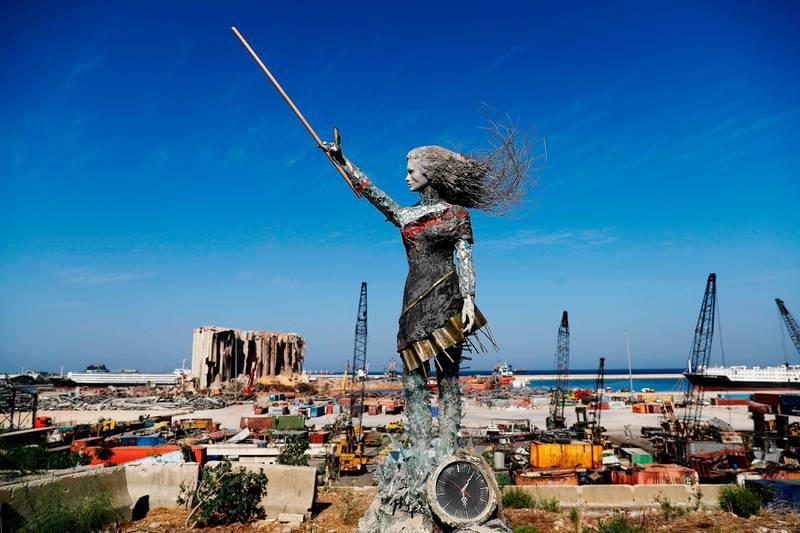 A statue of a woman made out of glass and rubble that resulted from the Beirut port mega explosion August 04, is placed opposite to the site of the blast in the Lebanese capital's harbour to mark the one year anniversary of the beginning of the anti-government protest movement across the country on October 20, 2020. Hundreds marched in Beirut on the weekend to mark the first anniversary of a non-sectarian protest movement that has rocked the political elite but has yet to achieve its goal of sweeping reform. A whirlwind of hope and despair has gripped the country in the year since protests began, as an economic crisis and a devastating port explosion two months ago pushed Lebanon deeper into decay.  / AFP / JOSEPH EID