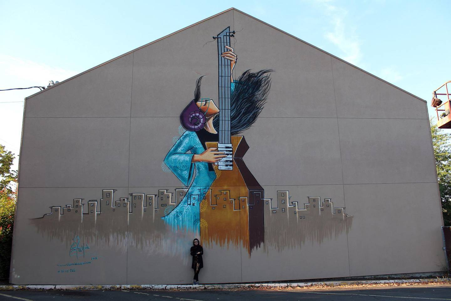Shamsia Hassani in 2018 next to a finished mural in Eugene Oregon USA. Picture courtesy of Shamsia Hassani