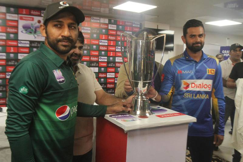 Sri Lanka captain Lahiru Thirimanne, right, and his Pakistani rival Sarfaraz Ahmed stand with a trophy, in Karachi, Pakistan, Thursday, Sept. 26, 2019. Thirimanne wants the focus to move from security in Pakistan to the cricket itself when their three-match ODI series starts Friday. (AP Photo/Fareed Khan)