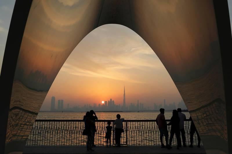 In this Friday, Oct. 18, 2019, photo, people enjoy a city skyline view with the World's tallest building Burj Khalifa, in Dubai, United Arab Emirates. (AP Photo/Kamran Jebreili)