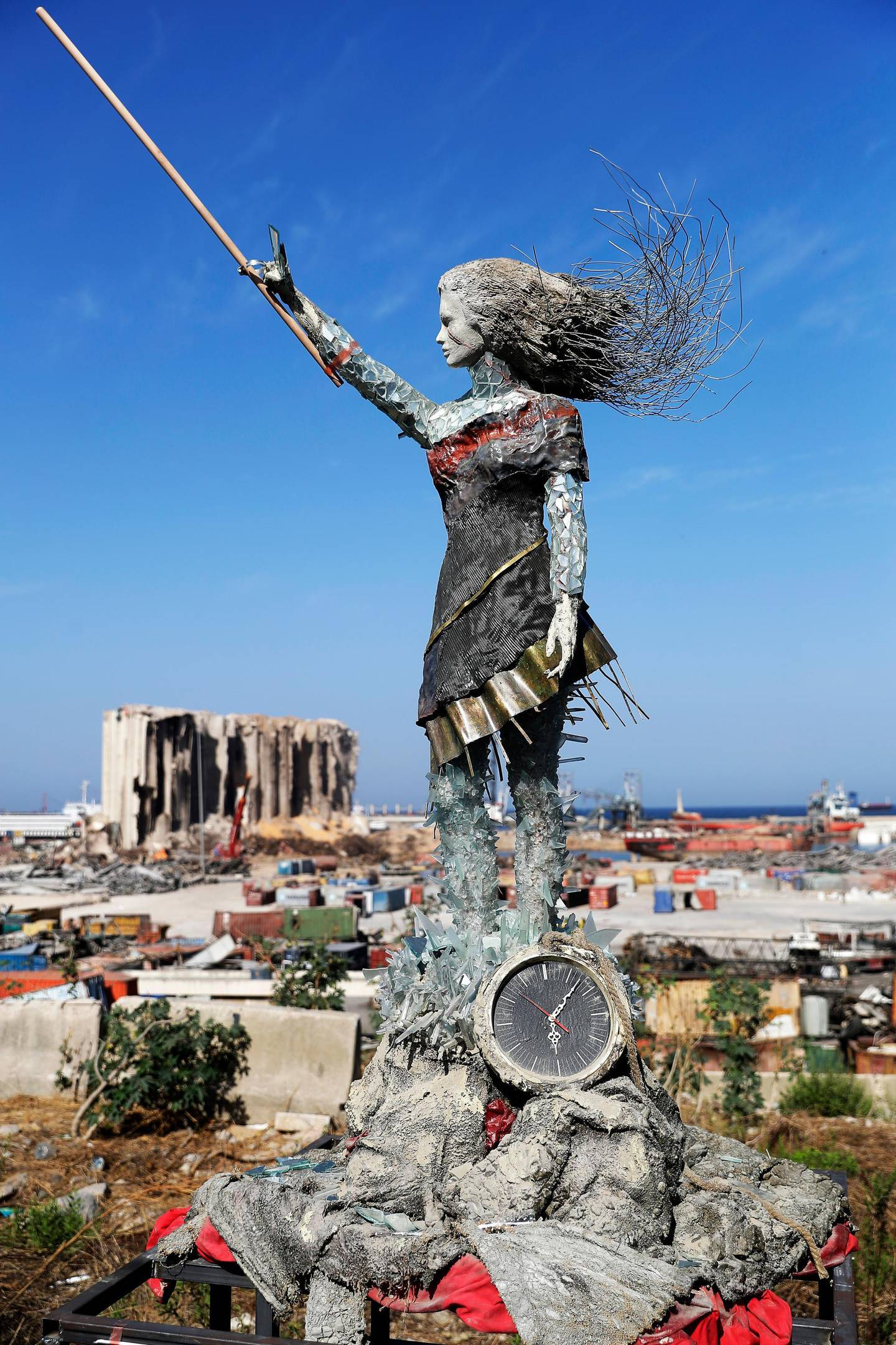A statue of a woman by Lebanese artist Hayat Nazer, made out of leftover glass, rubble, and a broken clock marking the time (6:08 PM) of the mega explosion at the port of Beirut is placed opposite to the site of the blast in the Lebanese capital's harbour, to mark the one year anniversary of the beginning of the anti-government protest movement across the country, on October 20, 2020. - Hundreds marched in Beirut on the weekend to mark the first anniversary of a non-sectarian protest movement that has rocked the political elite but has yet to achieve its goal of sweeping reform. A whirlwind of hope and despair has gripped the country in the year since protests began, as an economic crisis and a devastating port explosion two months ago pushed Lebanon deeper into decay. (Photo by JOSEPH EID / AFP) / RESTRICTED TO EDITORIAL USE - MANDATORY MENTION OF THE ARTIST UPON PUBLICATION - TO ILLUSTRATE THE EVENT AS SPECIFIED IN THE CAPTION