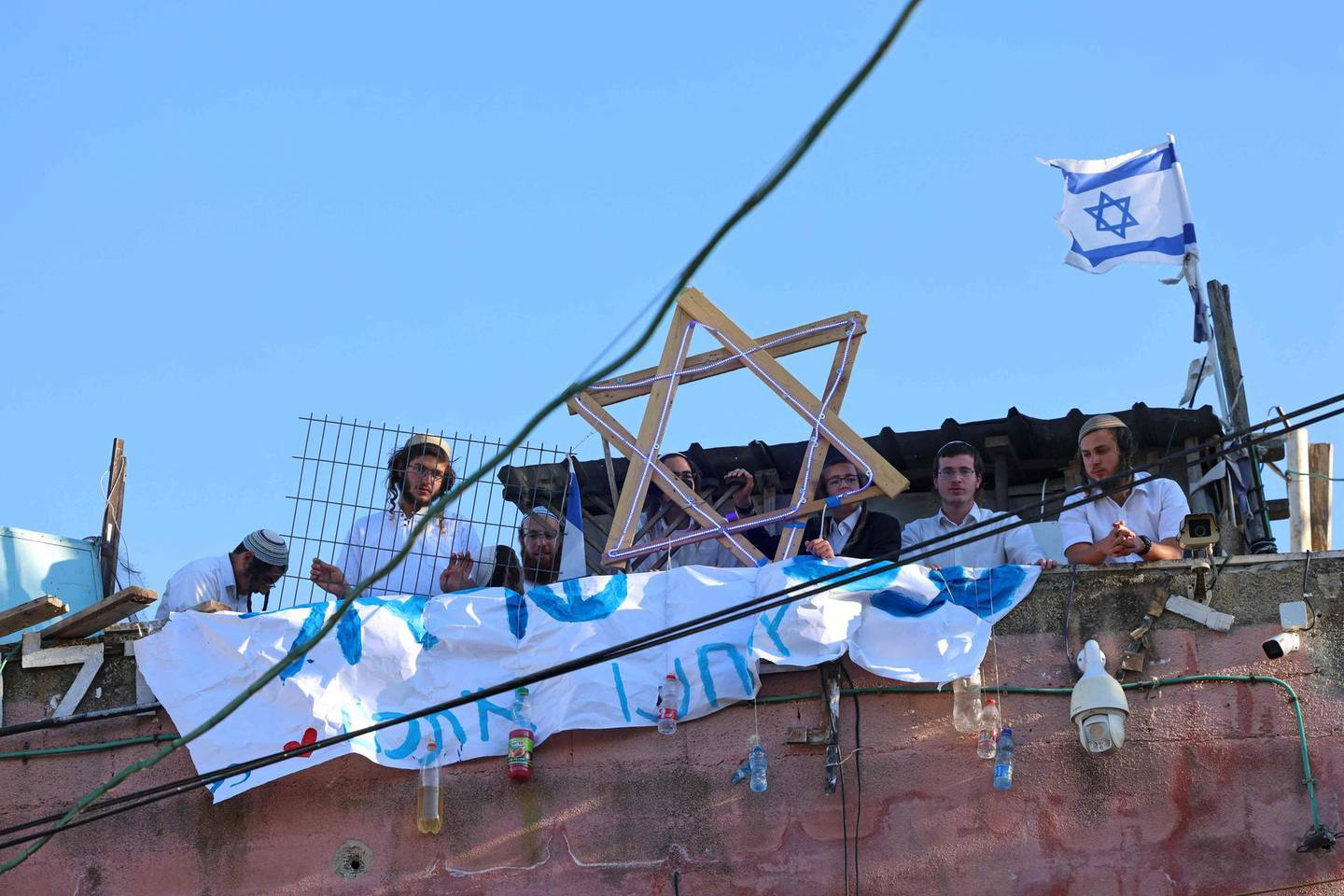 Israeli settlers sit on the rooftop of a house decorated with the Star of David in the Sheikh Jarrah neighbourhood of east Jerusalem on May 15, 2021.  / AFP / EMMANUEL DUNAND