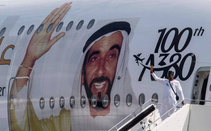A visitor poses for a photo in front of an Emirates A380 Airbus passenger aircraft decorated with a giant portrait of UAE founding father Zayed bin Sultan Al Nahyan, to celebrate the centenary of his birth, at the ILA Berlin International Aerospace Exhibition at Schoenefeld airport near Berlin on April 25, 2018. According to the organisers, over 1,000 exhibitors will showcase their expertise – from civil aviation to defense, security and space, and from major corporations to highly specialized suppliers. The fair is running from April 25 to 29, 2018. / AFP PHOTO / John MACDOUGALL