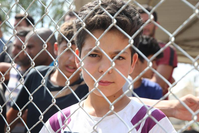 epa08504290 A refugee boy from Syria looks through a fence from inside the Pournara refugee camp in the village of Kokkinotrimithia, Cyprus,23 June 2020. Cypriot authorities reported that no cases of the coronavirus Covid-19 disease have been recorded in the accommodation centre.  EPA/KATIA CHRISTODOULOU