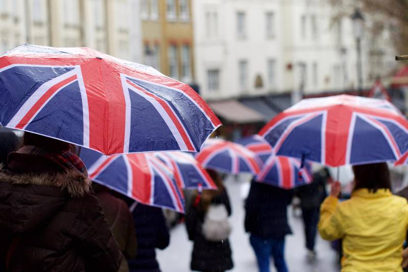 People Walking On Road With Umbrella. Getty Images