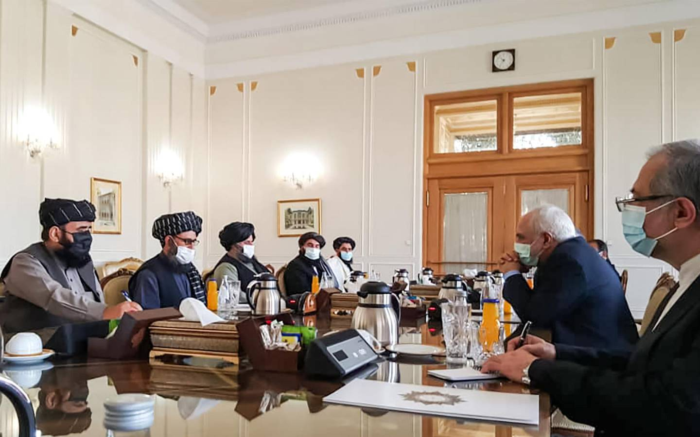 """A picture obtained by AFP from the Iranian news agency Tasnim on January 31, 2021, shows  Iran' Foreign Minister Mohammad Javad Zarif (2nd-R) meeting with Mullah Abdul Ghani Baradar (2nd-L) of the Taliban in Tehran. Iran's Foreign Minister Mohammad Javad Zarif called for the formation of an """"all-inclusive"""" Afghan government during a meeting with a Taliban delegation in Tehran. A delegation from the movement headed by its co-founder Mullah Abdul Ghani Baradar arrived in Iran on January 26 to exchange """"views on the peace process in Afghanistan"""" at the invitation of the ministry. / AFP / TASNIM NEWS / -"""