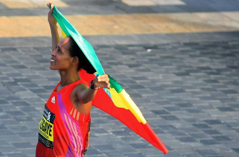 Tirfi Tsegaye Beyene of Ethiopia carries her national flag after she wins the Standard Chartered Dubai Marathon in Dubai, United Arab Emirates, Friday Jan. 25, 2013. (AP Photo) *** Local Caption ***  Mideast Emirates Dubai Marathon.JPEG-0da46.jpg