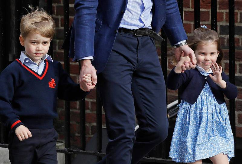FILE - In this  Monday, April 23, 2018 file photo, Britain's Prince William arrives with Prince George and Princess Charlotte at the Lindo wing at St Mary's Hospital in London. Kensington Palace said Wednesday May 16, 2018, that four-year-old George will be a page boy and three-year-old Charlotte will be a bridesmaid at the wedding of Prince Harry and Meghan Markle on Saturday. (AP Photo/Kirsty Wigglesworth, File)