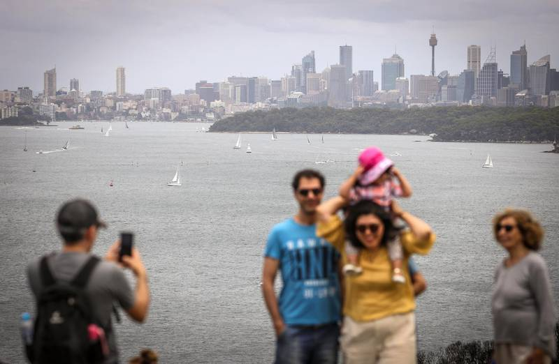 SYDNEY, AUSTRALIA - DECEMBER 26: People pose for photographs in front of yachts and ferries as they sail on Sydney Harbour during Boxing Day on December 26, 2020 in Sydney, Australia. Australians celebrate Boxing Day with many taking advantage of the post-Christmas sale prices in what is usually the busiest day of the year for retailers in Australia. Extra safety protocols have been introduced this year, due to the ongoing COVID-19 pandemic. In Sydney, thousands of people usually gather around and on the harbour to watch the start of the Sydney to Hobart yacht race. This year's race was cancelled for the first time in its 76 year history due to the current COVID-19 cluster outbreak in NSW. (Photo by David Gray/Getty Images)