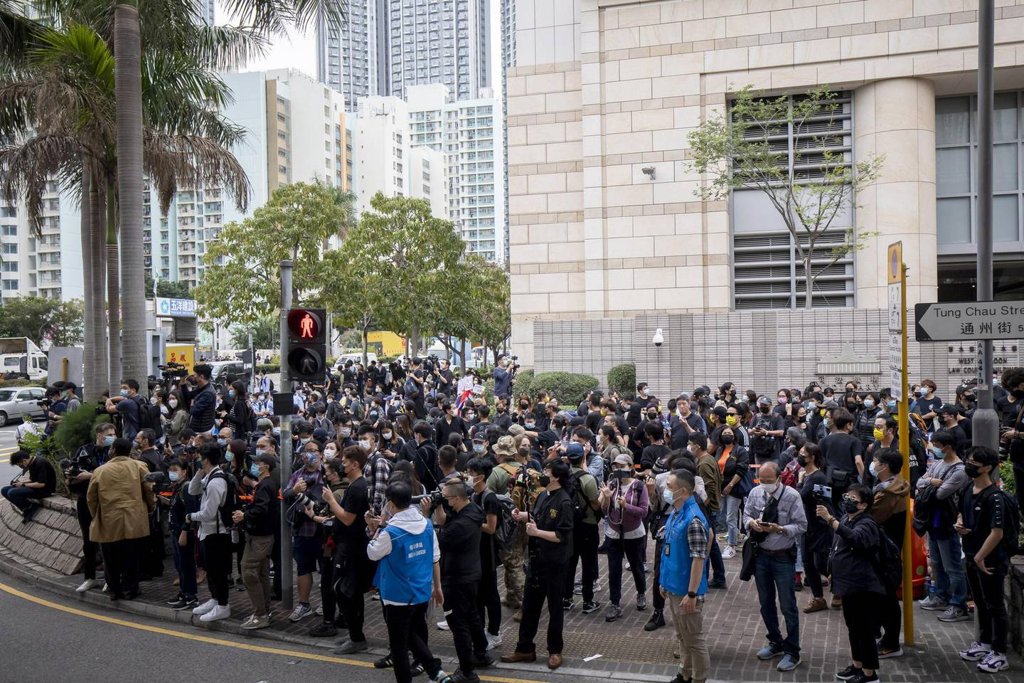 People gather outside the West Kowloon Magistrates' Courts during a hearing for 47 opposition activists charged with violating the city's national security law in Hong Kong, China, on Monday, March 1, 2021. Defiant Hong Kong protesters risked arrest outside a local court in the biggest demonstration in months, as dozens of the city's most prominent pro-democracy activists were jailed on subversion charges and authorities in Beijing moved to limit the opposition's role in future elections. Photographer: Paul Yeung/Bloomberg