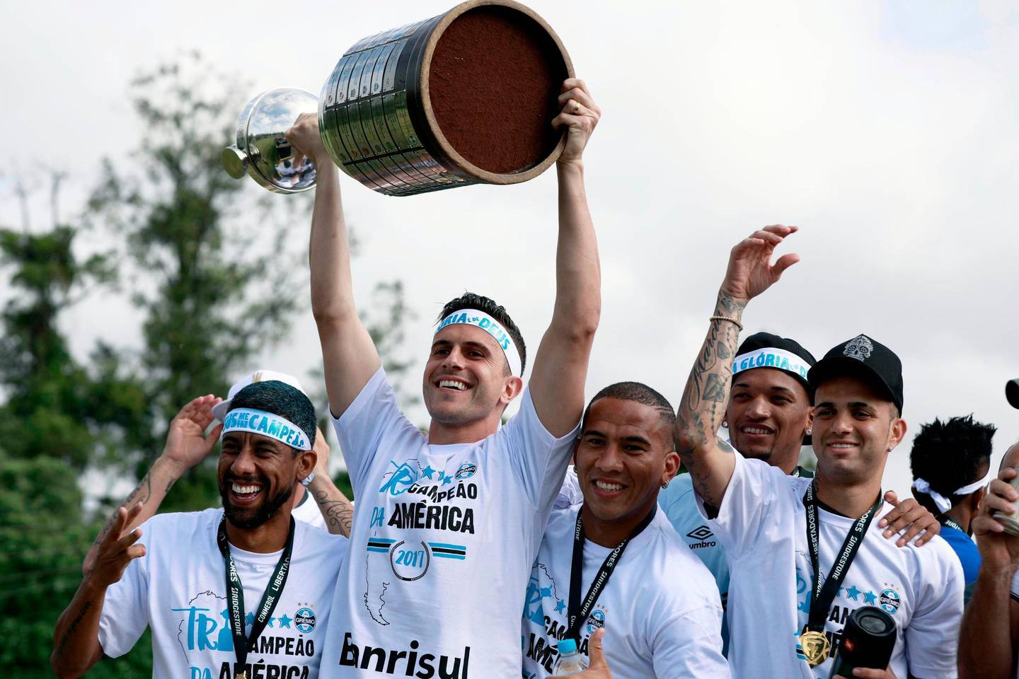 TOPSHOT - Brazil's Gremio goalkeeper Marcelo Grohe (2-L) raises the Copa Libertadores 2017 trophy next to his teammates, as he celebrates their victory in Porto Alegre, Brazil on November 30, 2017.  Brazilian side Gremio won their third Copa Libertadores crown on Wednesday with a 2-1 triumph over Argentina's Lanus in La Fortaleza stadium. With the victory, Gremio qualified directly into the semi-finals of the Club World Cup in December, where they'll face either Africa's Wydad Casablanca or CONCACAF representative Pachuca of Mexico. / AFP PHOTO / ITAMAR AGUIAR