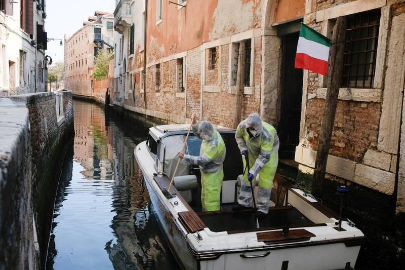 Municipal workers wearing protective gears sanitize a boat as the Italian government allows the reopening of some shops while a nationwide lockdown continues following the outbreak of the coronavirus disease (COVID-19), in Venice, Italy, April 14, 2020. REUTERS/Manuel Silvestri