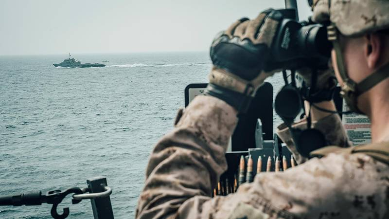 A U.S. Marine observes an Iranian fast attack craft from USS John P. Murtha during a Strait of Hormuz transit, Arabian Sea off Oman, in this picture released by U.S. Navy on July 18, 2019.. Donald Holbert/U.S. Navy/Handout via REUTERS ATTENTION EDITORS- THIS IMAGE HAS BEEN SUPPLIED BY A THIRD PARTY.