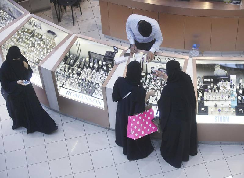Female shoppers wearing traditional Saudi Arabian dress browse watches on sale at a luxury concession stand inside the Kingdom Centre shopping mall in Riyadh, Saudi Arabia, on Friday, Dec. 2, 2016. Saudi Arabia is working to reduce the Middle East's biggest economy's reliance on oil, which provides three-quarters of government revenue, as part of a plan for the biggest economic shakeup since the country's founding. Photographer: Simon Dawson/Bloomberg