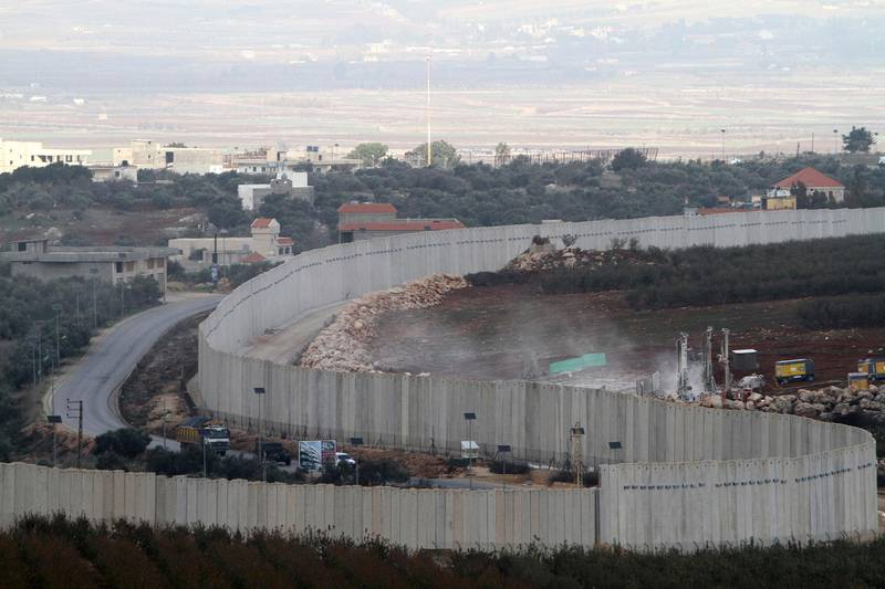 """Israeli military diggers work on the Lebanese-Israeli border next to a wall that was built by Israel in the southern village of Kafr Kila, Lebanon, Tuesday, Dec. 4, 2018. The Israeli military launched an operation on Tuesday to """"expose and thwart"""" tunnels it says were built by the Hezbollah militant group that stretch from Lebanon into northern Israel. (AP Photo/Mohammed Zaatari)"""