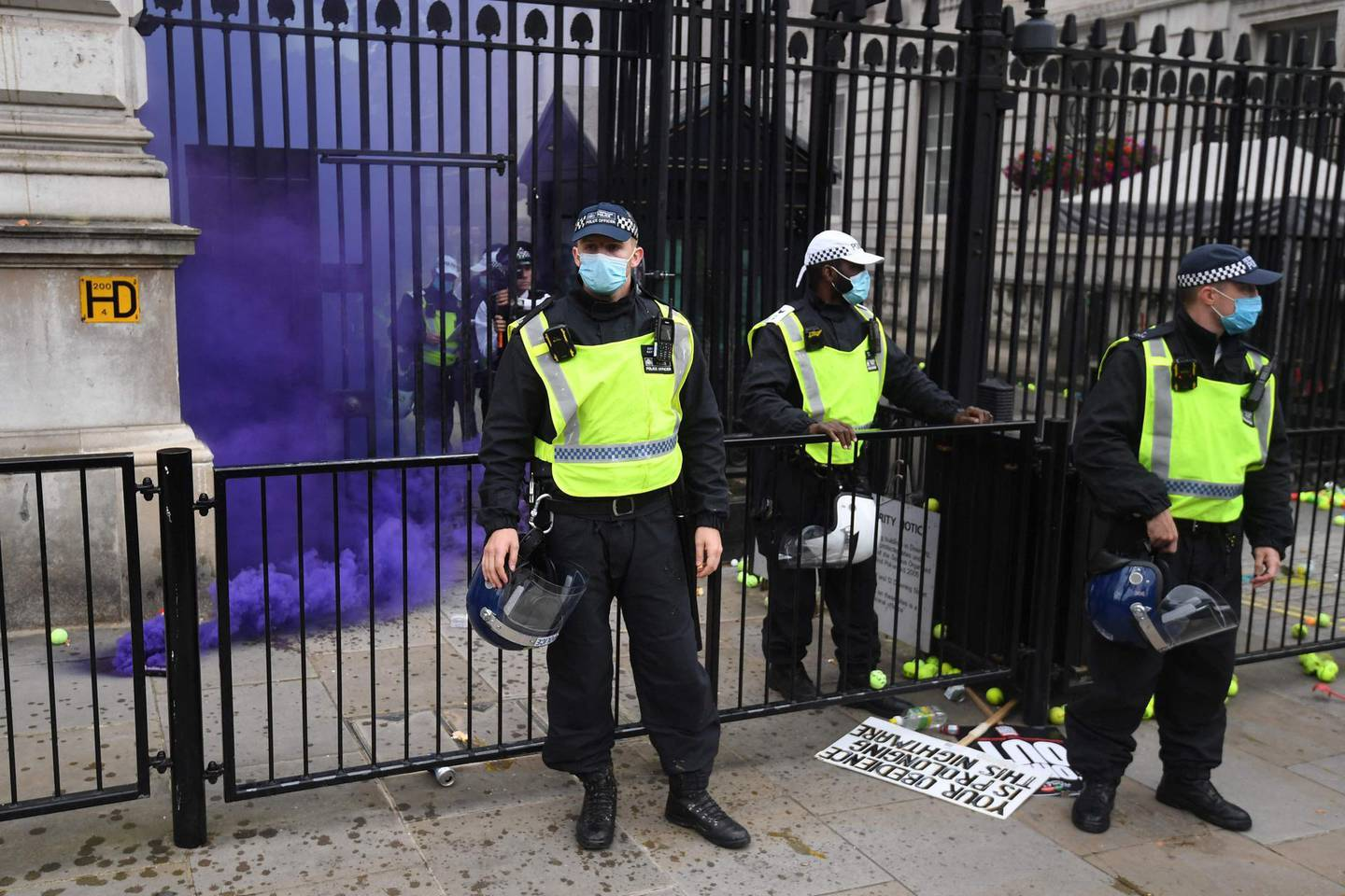 A smoke canister goes off during an anti-Vaccine and anti-lockdown demonstration outside Downing street in central London, on June 26, 2021.  / AFP / DANIEL LEAL-OLIVAS