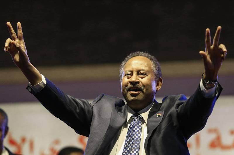 (FILES) This file photo taken on December 25, 2019 shows Sudanese Prime Minister Abdullah Hamdock flashing the victory sign during a ceremony marking the first anniversary of the uprising that toppled Omar al-Bashir. Sudan's Prime Minister Abdallah Hamdok survived unharmed an assassination attempt using explosives in the capital Khartoum on March 9, 2020, according to his top aide. A cabinet official also confirmed to AFP that Hamdok had escaped an attack.  / AFP / ASHRAF SHAZLY