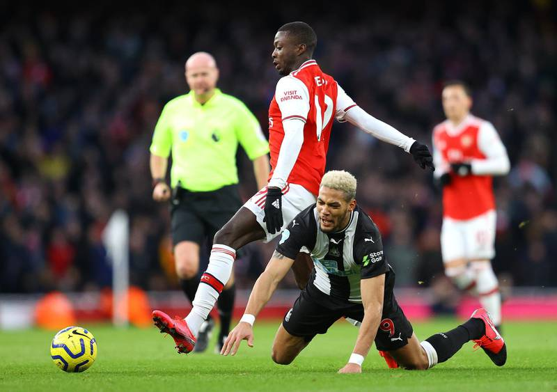 LONDON, ENGLAND - FEBRUARY 16: Joelinton of Newcastle United is tackled by Nicolas Pepe of Arsenal during the Premier League match between Arsenal FC and Newcastle United at Emirates Stadium on February 16, 2020 in London, United Kingdom. (Photo by Richard Heathcote/Getty Images)