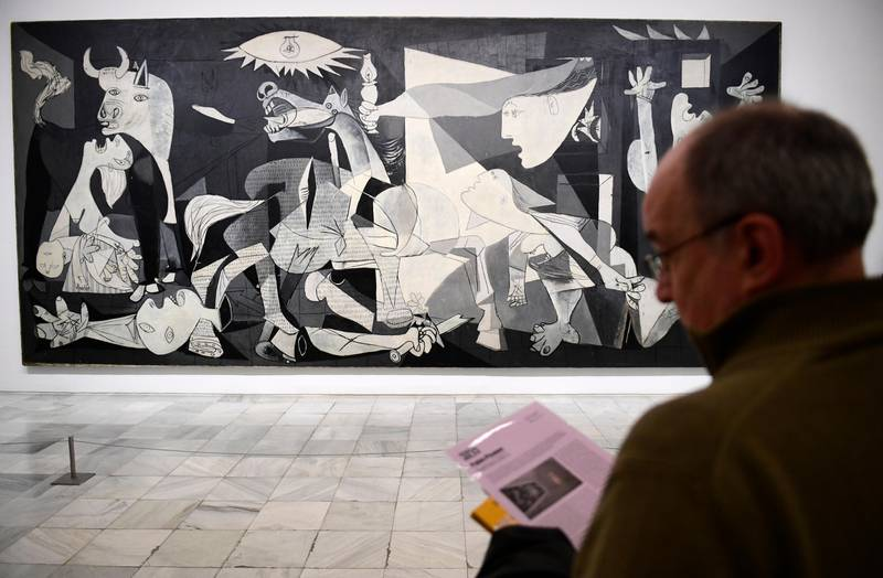 """A man looks at Spanish artist Pablo Picasso's painting, """"Guernica"""" at Reina Sofia museum in Madrid on March 24, 2017.Close to 80 years ago, Picasso painted Guernica in a Paris attic, a haunting work of art that soon became a universal howl against the ravages of war, from 1937 Spain to 2017 Syria. / AFP PHOTO / PIERRE-PHILIPPE MARCOU / RESTRICTED TO EDITORIAL USE - MANDATORY MENTION OF THE ARTIST UPON PUBLICATION - TO ILLUSTRATE THE EVENT AS SPECIFIED IN THE CAPTION"""