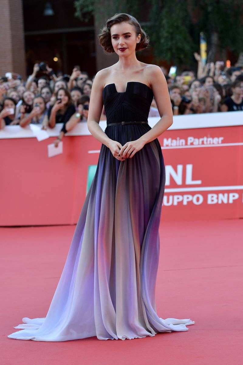 """Actress Lily Collins poses on the red carpet as she arrives for the screening of the movie """"Love, Rosie"""" presented at the Rome Film Festival, on October 19, 2014 in Rome. AFP PHOTO/ TIZIANA FABI (Photo by TIZIANA FABI / AFP)"""