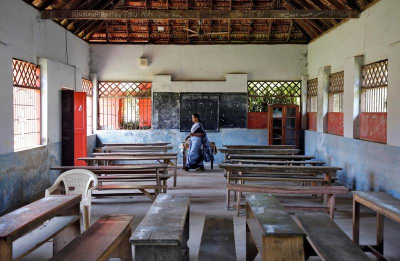 A staff member walks inside an empty classroom of a school after Kerala state government ordered the closure of schools across the state, amid coronavirus fears, in Kochi, India March 12, 2020. REUTERS/Sivaram V