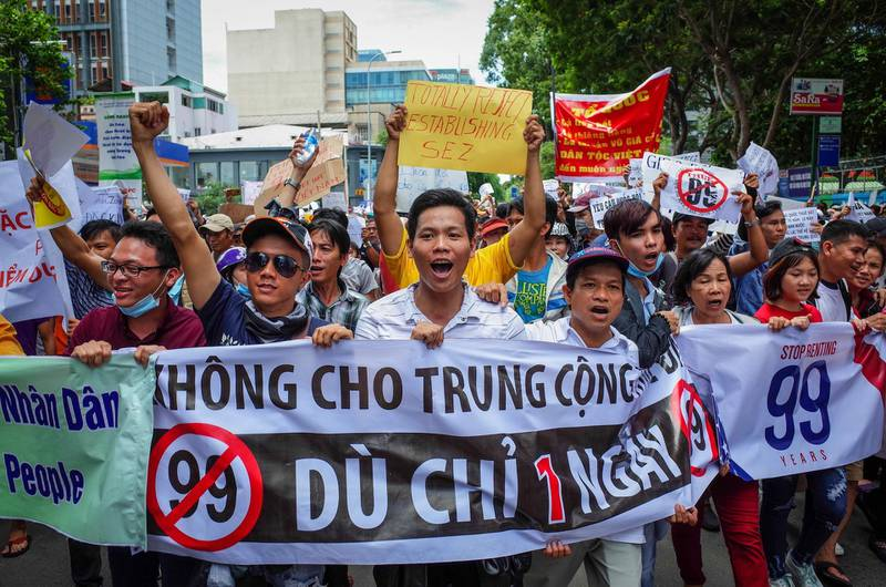 Vietnamese protesters shout slogans against a proposal to grant companies lengthy land leases during a demonstration in Ho Chi Minh City on June 10, 2018. The draft law at the centre of the furore would allow 99-year concessions in planned special economic zones, which some view as sweetheart deals for foreign and specifically Chinese firms. / AFP / Kao NGUYEN