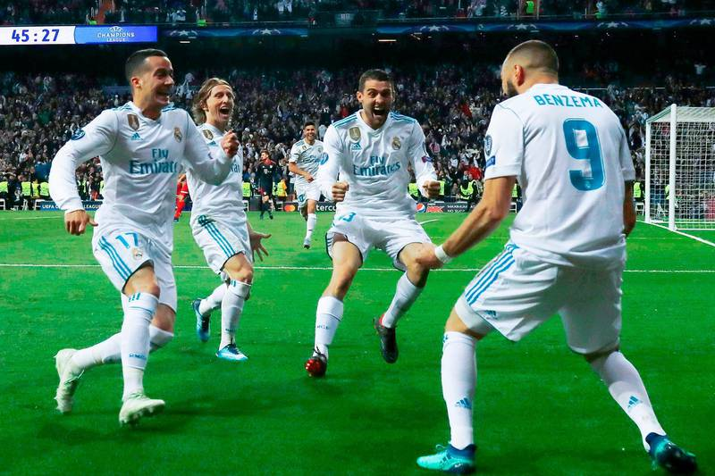 Real Madrid's French forward Karim Benzema (R) celebrates with Real Madrid's Spanish midfielder Lucas Vazquez (L), Real Madrid's Croatian midfielder Luka Modric (C) and Real Madrid's Croatian midfielder Mateo Kovacic after scoring a second goal during the UEFA Champions League semi-final second leg football match between Real Madrid and Bayern Munich at the Santiago Bernabeu Stadium in Madrid on May 1, 2018. / AFP PHOTO / OSCAR DEL POZO