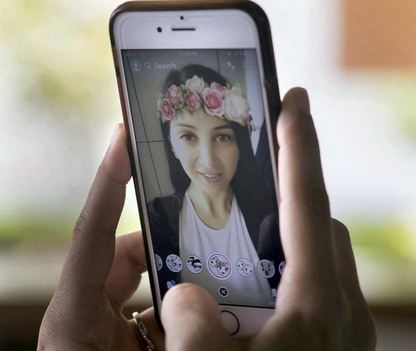 ABU DHABI, UNITED ARAB EMIRATES - AUGUST 14, 2018. A woman takes a selfie using Snapchat's face filter.(Photo by Reem Mohammed/The National)Reporter: Section:  NA
