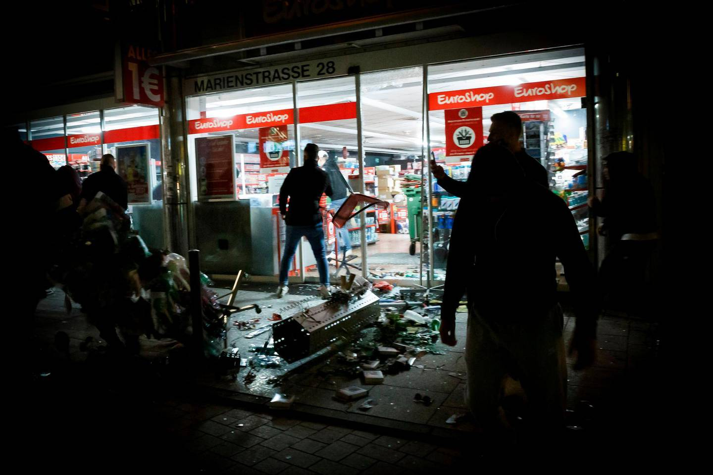 People stand in front of a shop that was plundered during riots on early June 21, 2020 in Stuttgart, southern Germany. Hundreds of people ran riot in Germany's Stuttgart city centre in the early hours of Sunday, June 21, 2020, throwing stones and bottles at police and plundering stores after smashing shop windows. - Germany OUT  / AFP / dpa / Julian RETTIG