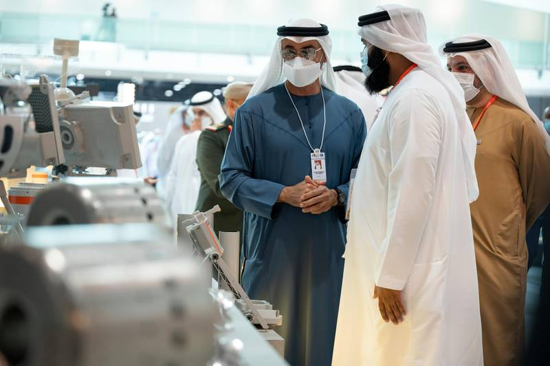 ABU DHABI, UNITED ARAB EMIRATES - February 22, 2021: HH Sheikh Hamed bin Zayed Al Nahyan, Member of Abu Dhabi Executive Council (L) tours the International Defence Exhibition and Conference (IDEX), at ADNEC. Seen with Faisal Al Bannai, Chief Executive and Managing Director of EDGE (back R).  ( Rashed Al Mansoori / Ministry of Presidential Affairs ) ---