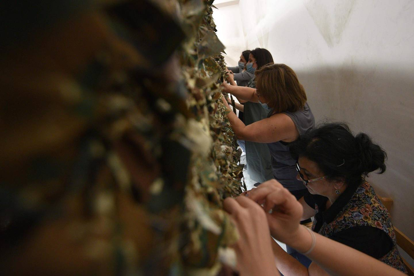 TOPSHOT - Armenian women make camouflage net to be sent to a frontline in Karabakh in Yerevan on October 18, 2020.  Baku and Yerevan have for decades been locked in a simmering conflict over Nagorno-Karabakh, an ethnically Armenian region of Azerbaijan which broke away from Baku in a 1990s war that claimed the lives of some 30,000 people. The Caucasus neighbours have defied international calls to halt hostilities and accused the other of starting new clashes that began September 27 and have seen the heaviest fighting since a 1994 truce.  / AFP / Karen MINASYAN