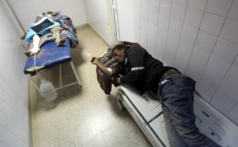 African migrant, who were injured after their vehicle was overturned during a truck collision, sleep on beds in a hospital room in the town of Beni Walid, 170 kilometres southeast of the capital Tripoli, on February 14, 2018. At least 19 migrants were killed and more than 100 injured when the truck transporting them crashed in Libya on February 14, a hospital said. More than 300 migrants, mostly Eritrean and Somali nationals, were on board the vehicle which overturned near the town of Bani Walid. / AFP PHOTO / MAHMUD TURKIA
