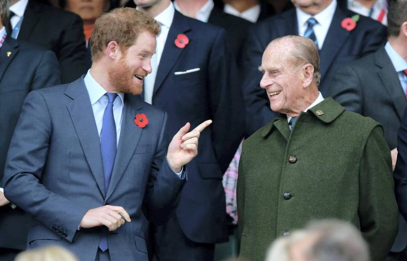 LONDON, ENGLAND - OCTOBER 31:  (EDITORS NOTE: Retransmission of #495101428 with alternate crop.) Prince Harry and Prince Phillip enjoy the atmosphere during the 2015 Rugby World Cup Final match between New Zealand and Australia at Twickenham Stadium on October 31, 2015 in London, United Kingdom.  (Photo by Phil Walter/Getty Images)