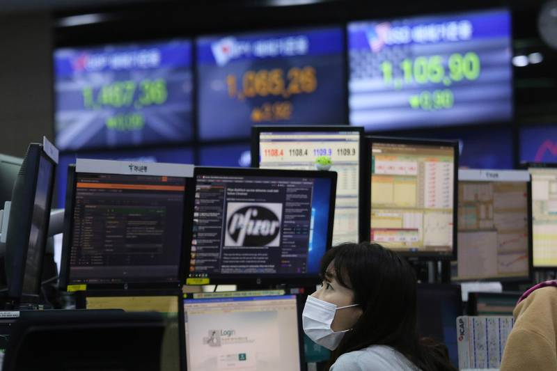 A currency trader watches monitors at the foreign exchange dealing room of the KEB Hana Bank headquarters in Seoul, South Korea, Thursday, Nov. 19, 2020. Asian stocks followed Wall Street lower on Thursday as anxiety about the economic fallout from rising coronavirus infections in the United States and Europe clashed with optimism about a possible vaccine. (AP Photo/Ahn Young-joon)