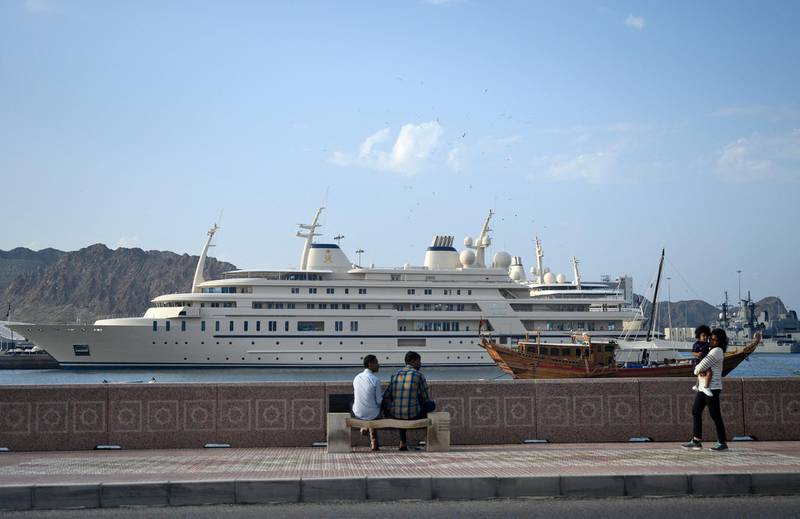 People walk on the waterfront near a yacht for Oman's Sultan Haitham bin Tarik Al Saidat in Muscat on February 21, 2020. (Photo by ANDREW CABALLERO-REYNOLDS / AFP)