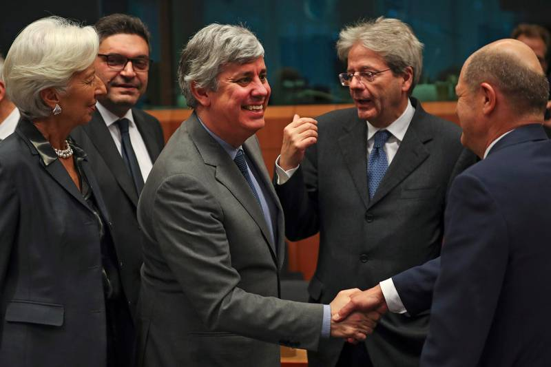 """FILE - In this Monday, Jan. 20, 2020 file photo Eurogroup President Mario Centeno, center, shakes hands with German Finance Minister Olaf Scholz, right, next to European Central Bank President Christine Lagarde, left, Cyprus' Economy Minister Constantinos Petrides, second left, and European Commissioner for Economy Paolo Gentiloni, second right, during a meeting of European Union Finance Ministers in Eurogroup format at the Europa building in Brussels. Governments from the 19 countries that use the euro overcame sharp differences to agree Thursday on measures that could provide more than a half-trillion euros ($550 billion) for companies, workers and health systems to cushion the economic impact of the virus outbreak. Mario Centeno, who heads the finance ministers' group from euro countries, called the package of measures agreed upon """"totally unprecedented... Tonight Europe has shown it can deliver when the will is there."""" (AP Photo/Francisco Seco, File)"""
