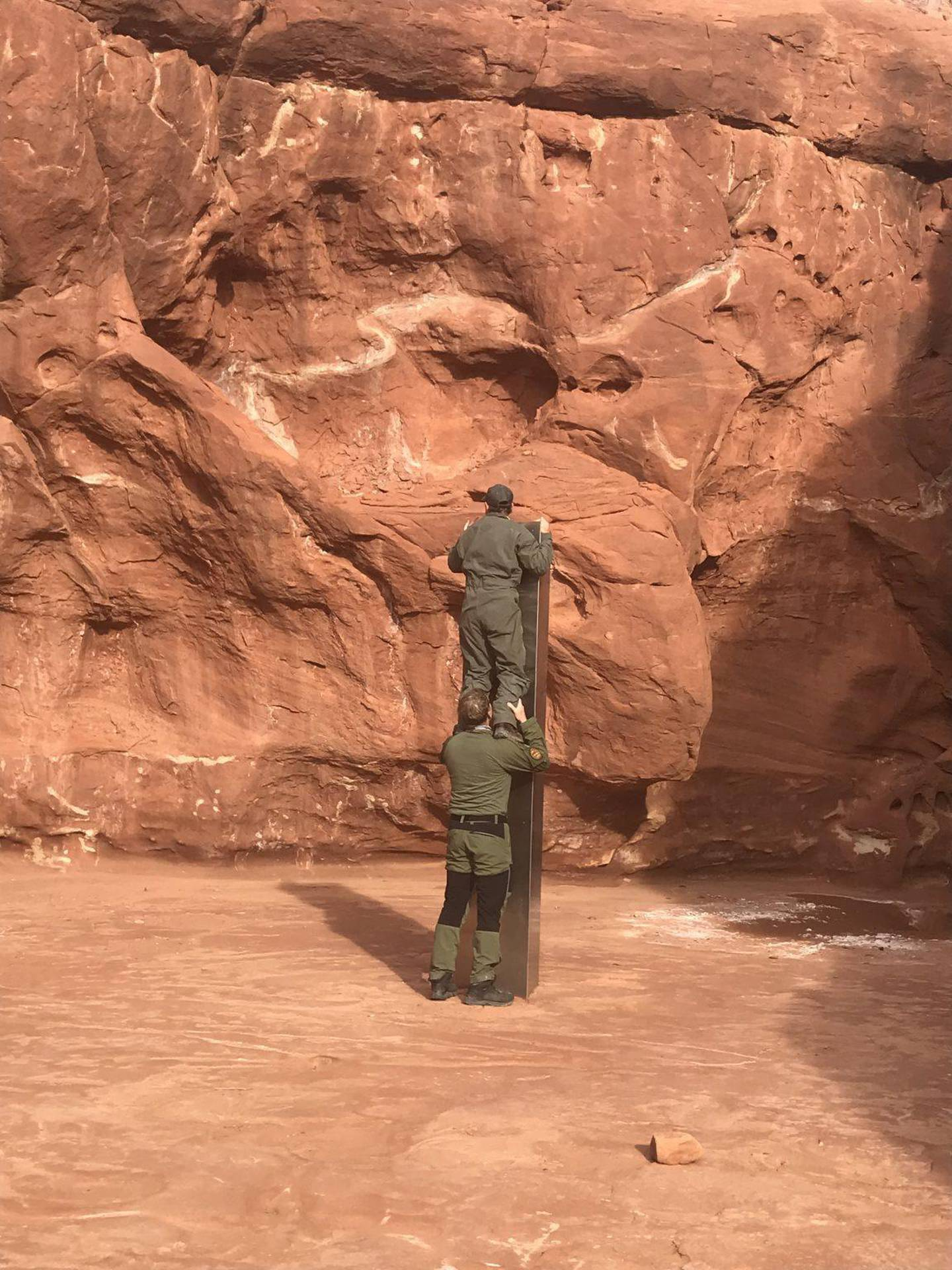 epa08839417 A handout photo made available by the Utah Department of Public Safety (DPS) shows wildlife officials inspecting a monolith discovered in southeastern Utah, USA, 18 November 2020 (issued 24 November 2020). According to a statement by DPS, Utah officials have discovered a monolith of unknown origin in the wild.  EPA/Utah Department of Public Safety HANDOUT  HANDOUT EDITORIAL USE ONLY/NO SALES