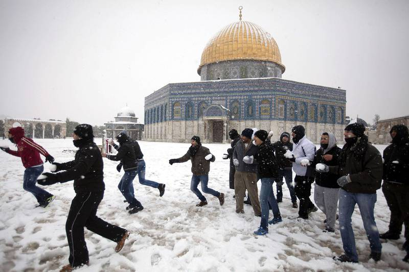 Palestinians play with snow outside the Dome of the Rock at the Al-Aqsa mosque compound in the old city of Jerusalem on January 10, 2013. Jerusalem was transformed into a winter wonderland after heavy overnight snowfall turned the Holy City and much of the region white, bringing hordes of excited children onto the streets. AFP PHOTO/AHMAD GHARABLI