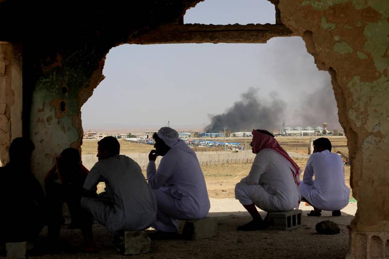 Jordanian residents of Jabir village watch aid deliveries to Syrians fleeing government offensive in the south as smoke from unknown fire rises, Tuesday, July 3, 2018. The UN says Syria government's Russian-backed offensive to recover southern territories from rebels has displaced 270,000 people, 60,000 of them headed near the sealed Jordanian borders.(AP Photo/Raad Adayleh)