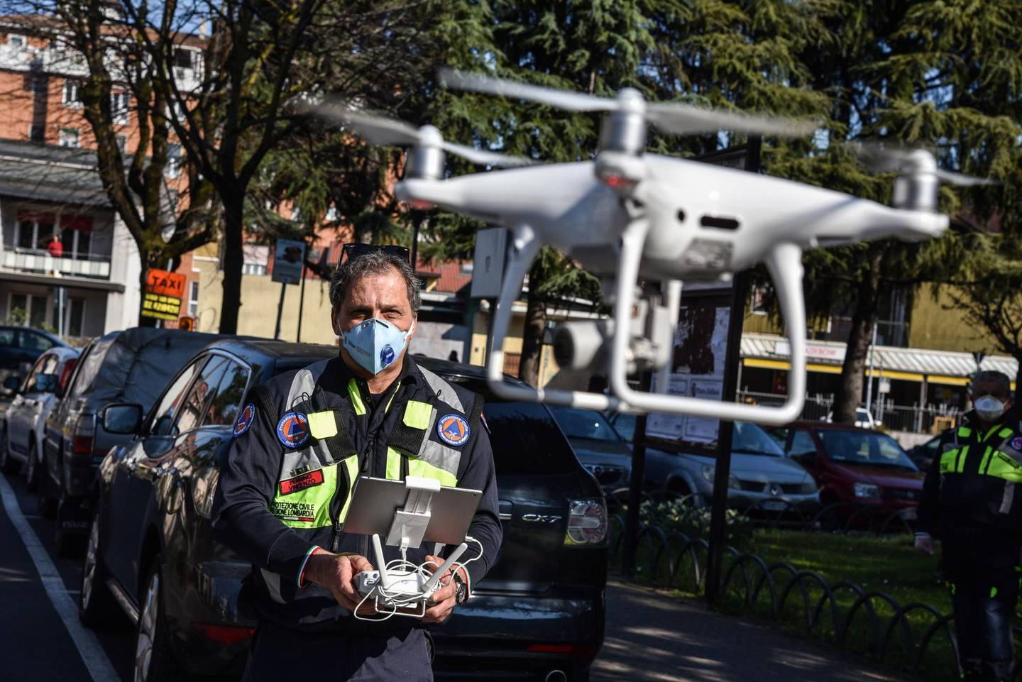 epa08319147 A drone pilot of the Civil Protection agency operates one of the three drones supplied to the municipality of Opera, near Milan, 24 March 2020. The drones are used to monitor citizens' compliance with the rules restricting movement amid the national lockdown implemented in a bid to slow down the ongoing pandemic of the COVID-19 disease caused by the SARS-CoV-2 coronavirus that is ravaging the Mediterranean country.  EPA/MATTEO CORNER