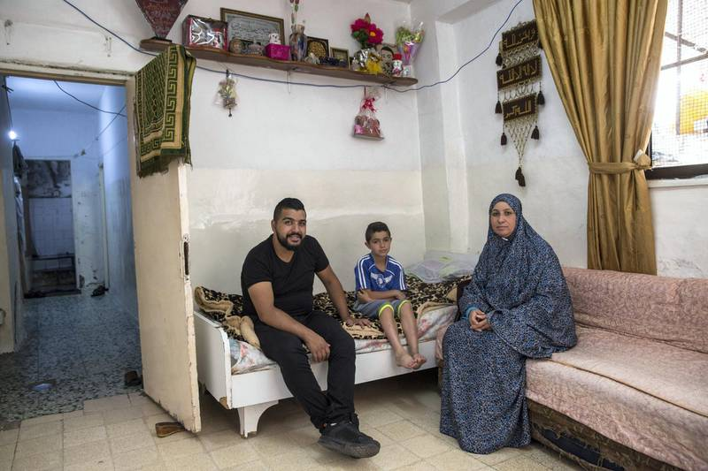 Motes Abu Khader,26, and his mother Nada.47, inside their hime in the Aida refugee camp near the Palestinian city of Bethlehem on June 23,2019. Eight family members live in the home . Photo by Heidi Levine for The National