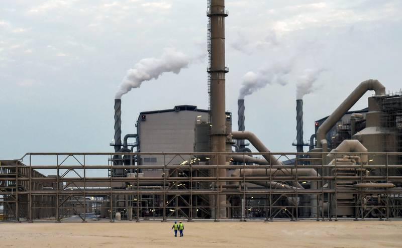 Emloyees walk outside the Maaden Aluminium Factory in Ras Al-Khair Industrial area near Jubail City, 570 kms east of the Saudi capital Riyadh, on November 23, 2016. - Maaden Aluminium is a joint venture between the Saudi Arabian Mining Company (Maaden) and Alcoa, the third largest producer of aluminium in the world. (Photo by FAYEZ NURELDINE / AFP)