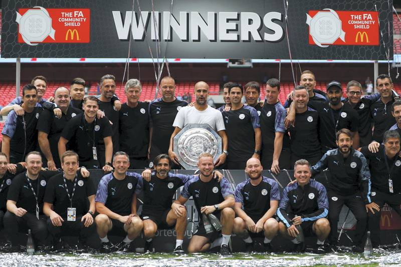 Manchester City's Spanish manager Pep Guardiola holds the trophy as he poses with his staff after winning the English FA Community Shield football match between Manchester City and Liverpool at Wembley Stadium in north London on August 4, 2019. (Photo by Adrian DENNIS / AFP) / NOT FOR MARKETING OR ADVERTISING USE / RESTRICTED TO EDITORIAL USE